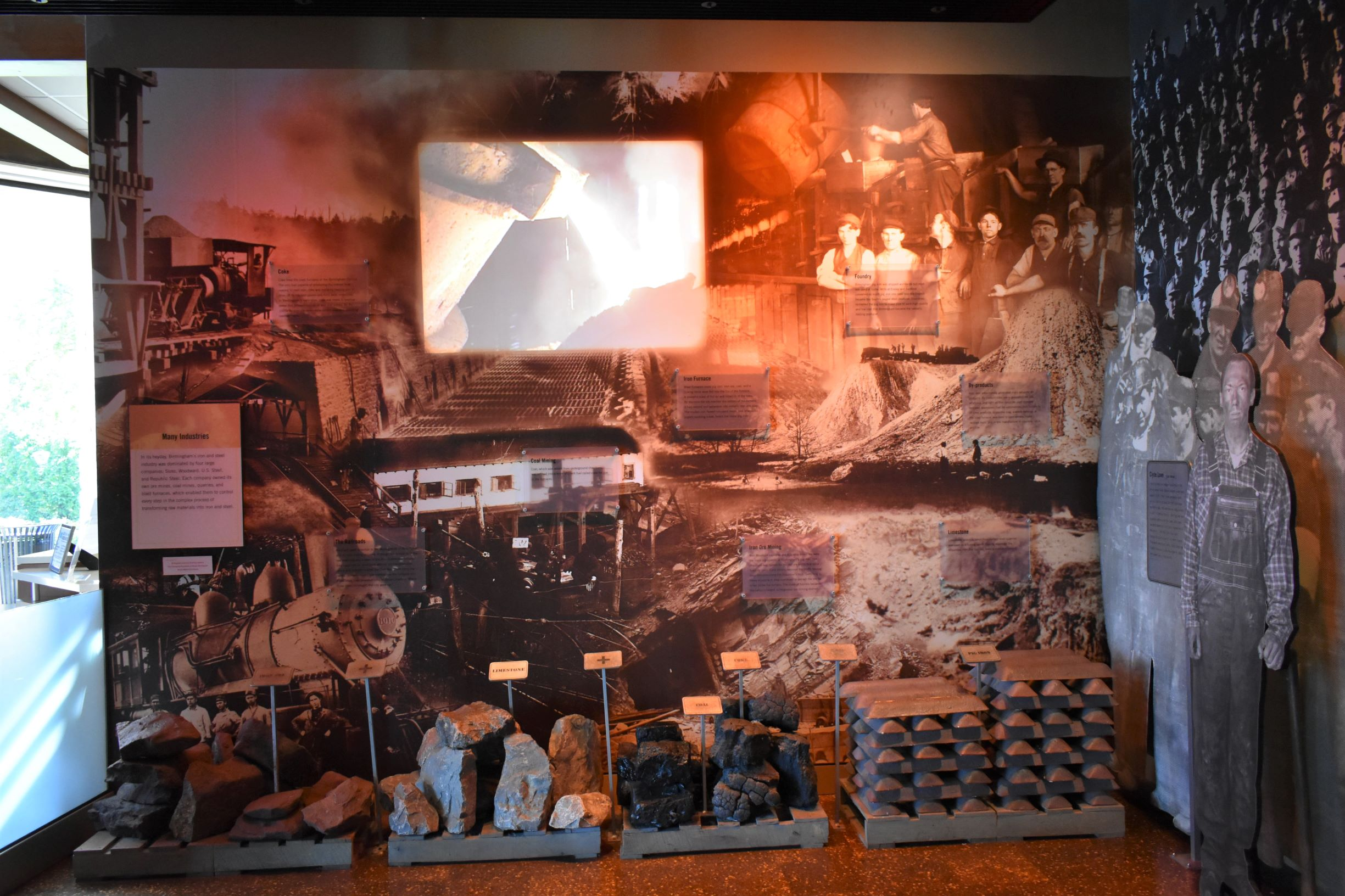 Interior of museum gallery. Large pieces of minerals sit on pallets in floor including iron ore, limestone, coal, and coke. On the right there is a stack of iron ingots. A video in center of wall shows molten iron pouring from a ladle.