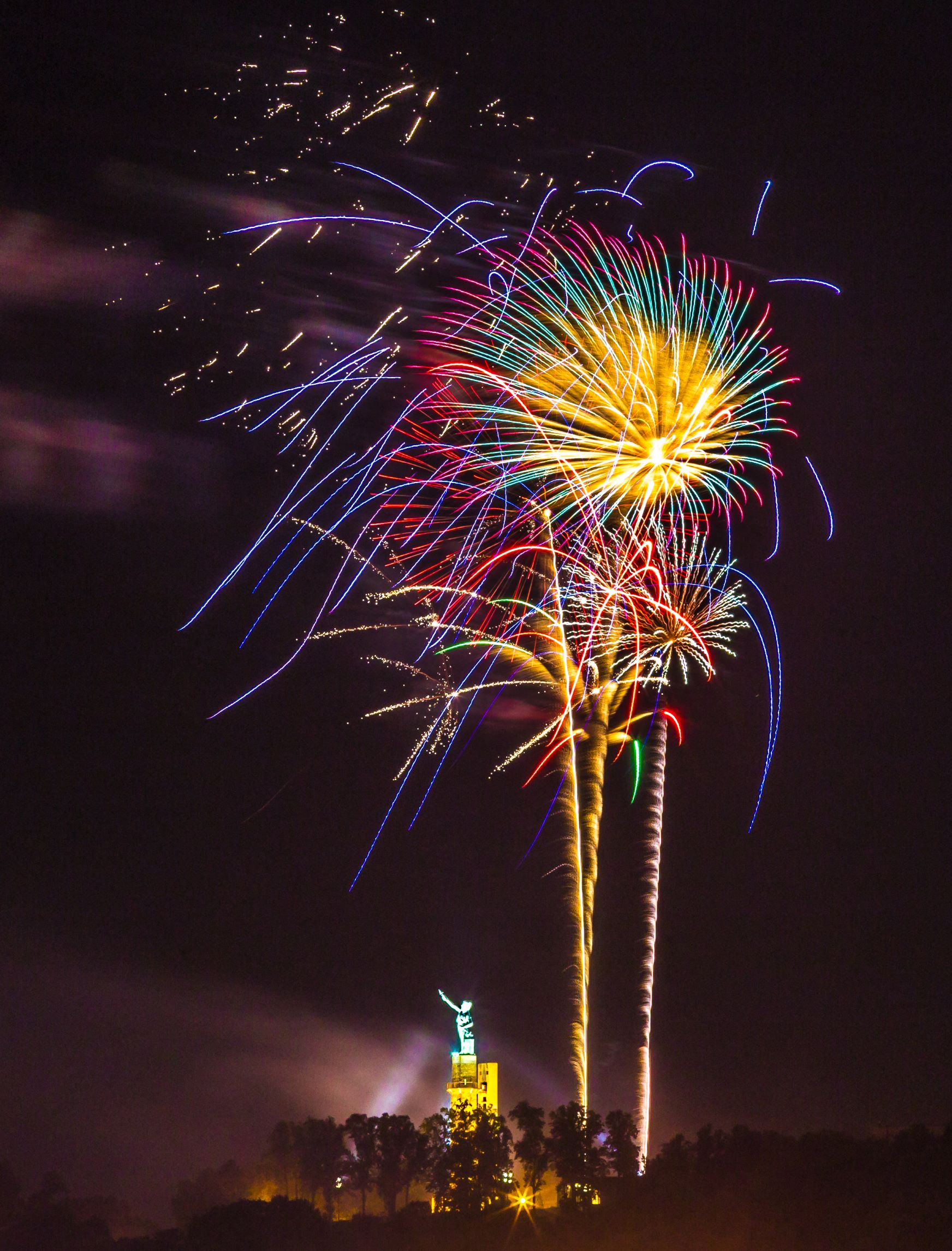 Pink, green, yellow, and blue fireworks over the statue of Vulcan with trees in the foreground