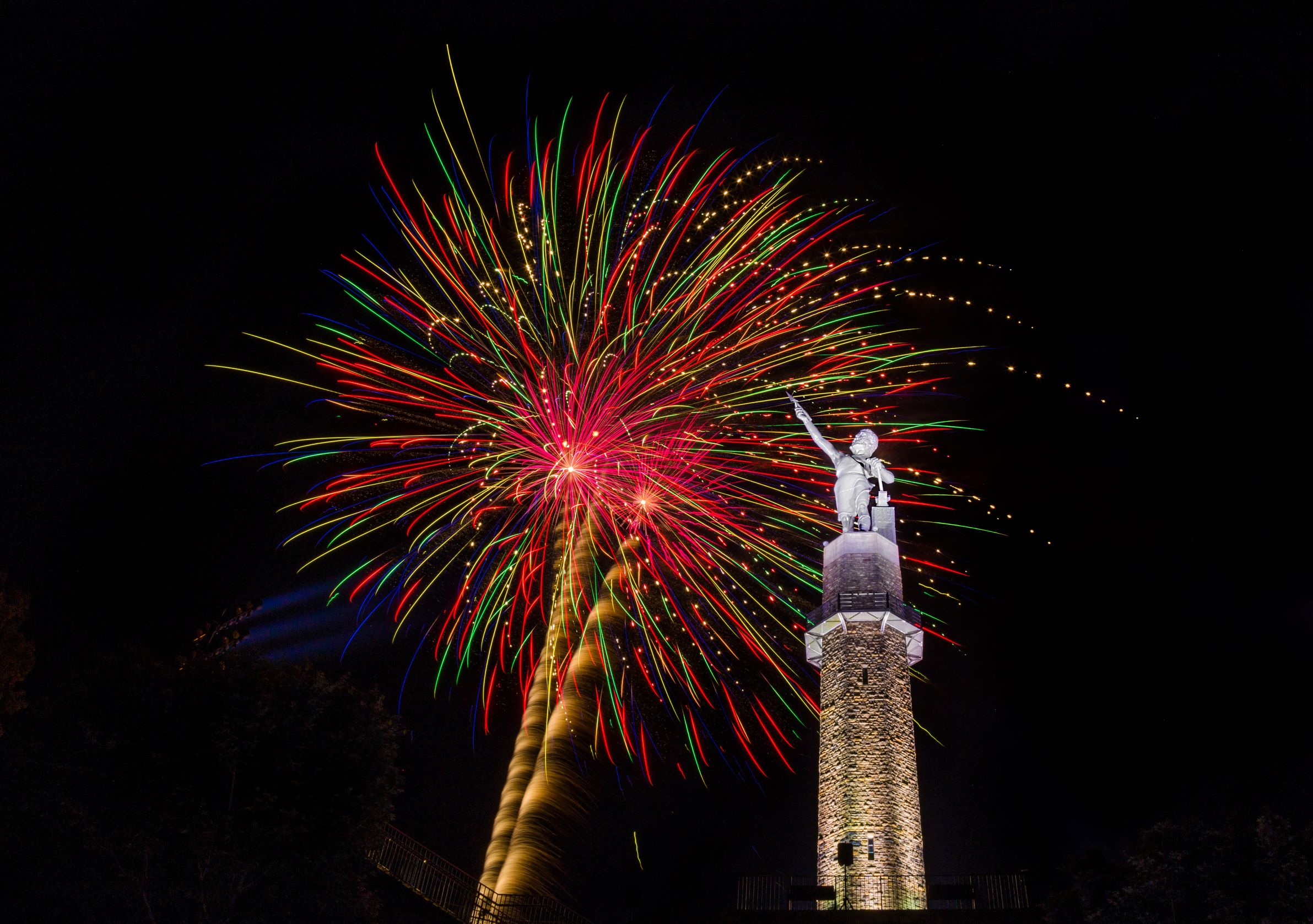 Red, pink, green, and blue fireworks over the statue of Vulcan